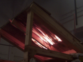 Demonstration of a flame-through (burn-through), passing from the roof covering to the underside of the roof deck. As constructed, this is not a Class A roof covering because it allowed flame penetration when subjected to a Class A burning brand. Photo: Stephen L. Quarles.